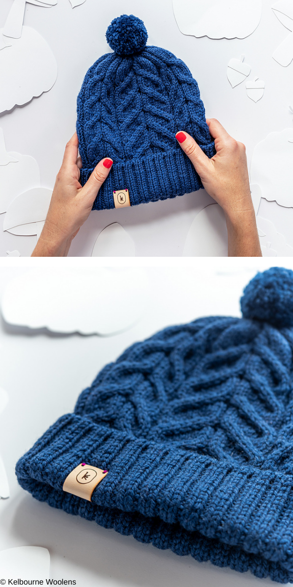 Dark blue beanie with pompon on white background